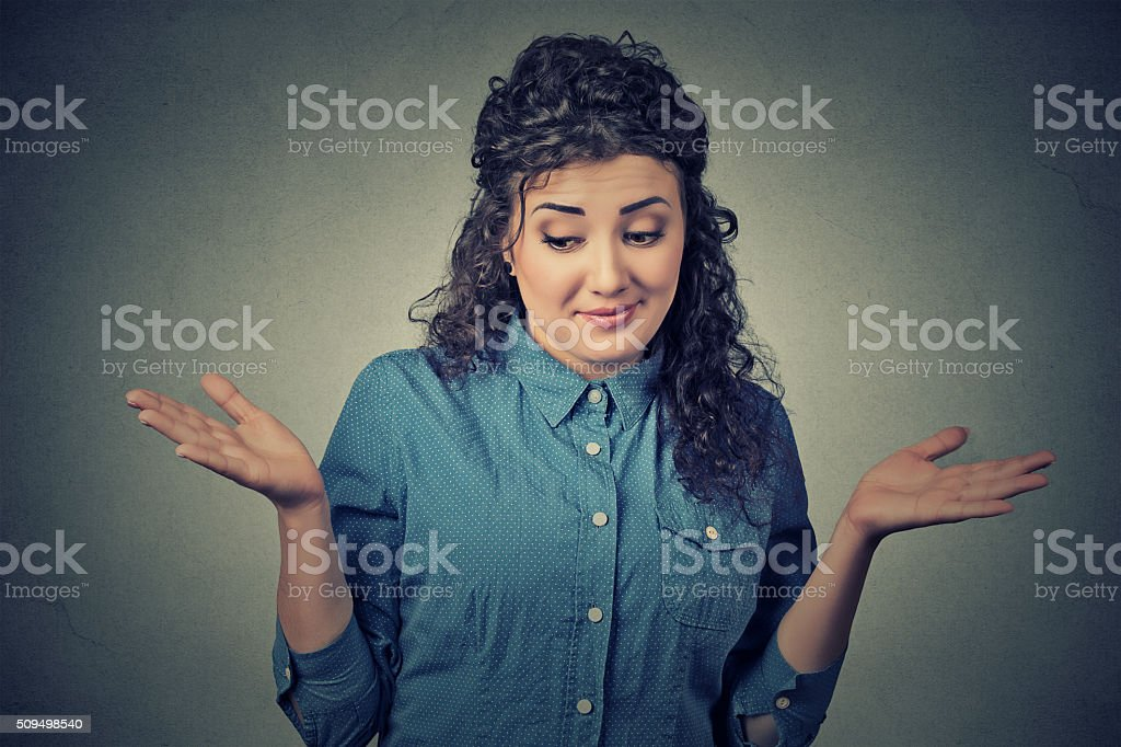dumb looking woman shrugs shoulders who cares so what stock photo