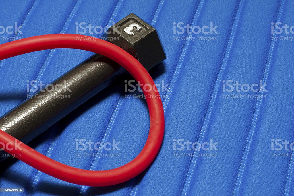 Dumbbell and red exercise tube lie on a blue mat. stock photo