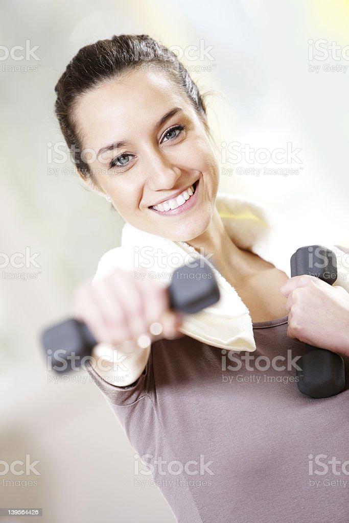 Haltère dans la main de la jeune femme souriante travail photo libre de droits