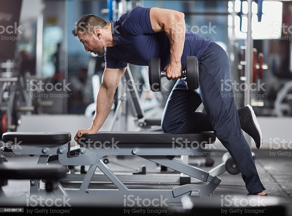 Dumbbell row in the gym stock photo