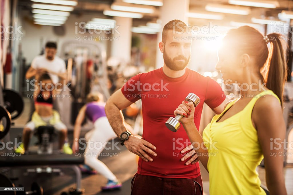 Dumbbell workout with personal trainer in a gym. stock photo