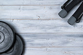 Dumbbells and weight plates on wooden background