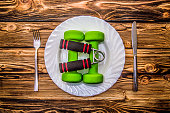 Dumbbells, ball and expander on a plate as breakfast, concept