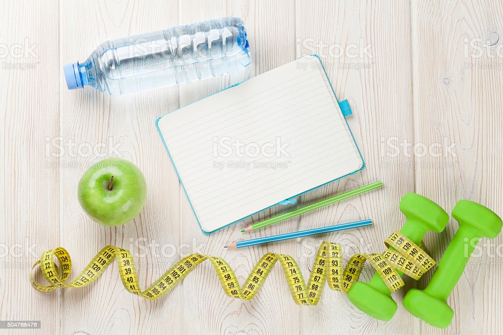 Dumbbells, water and notepad stock photo