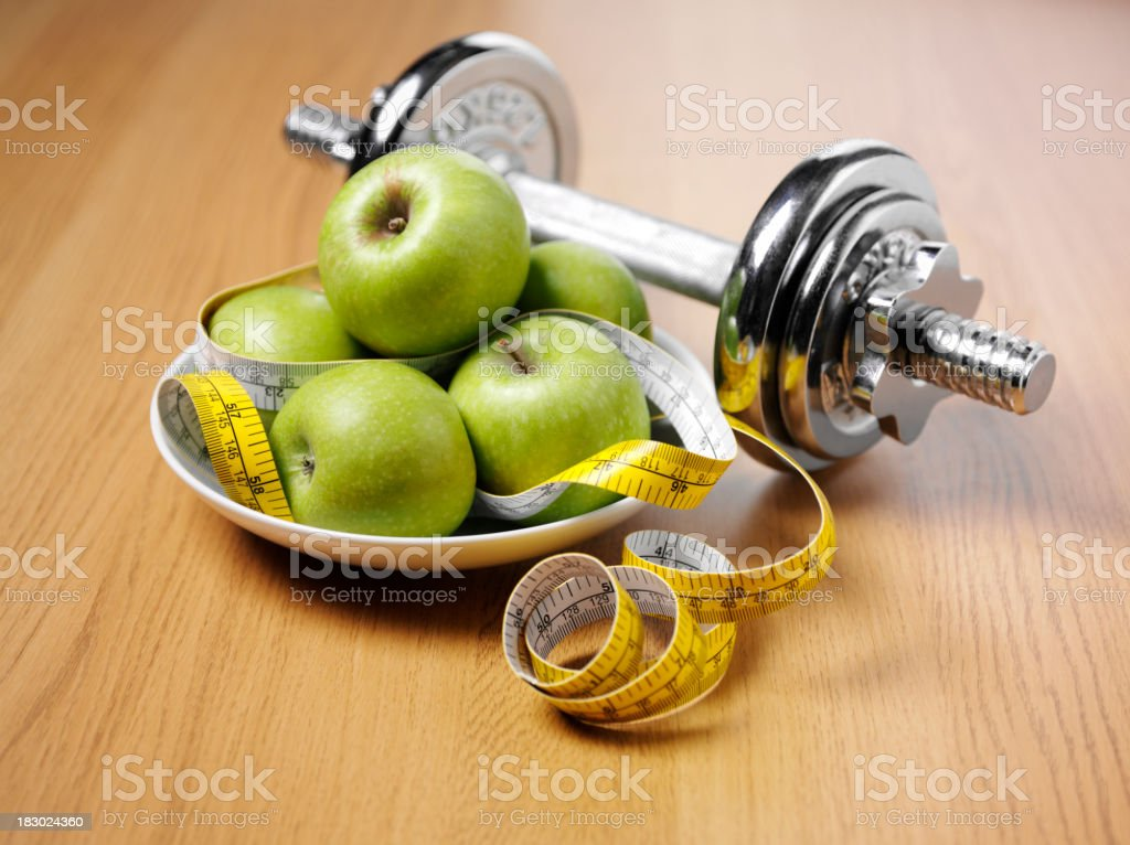 Dumbbells with Apples and Tape Measure stock photo