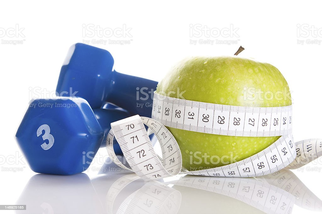 Dumbbells with green apple and measuring tape on white royalty-free stock photo