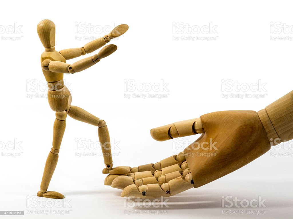 Dummy guy stepping on big wooden hand stock photo
