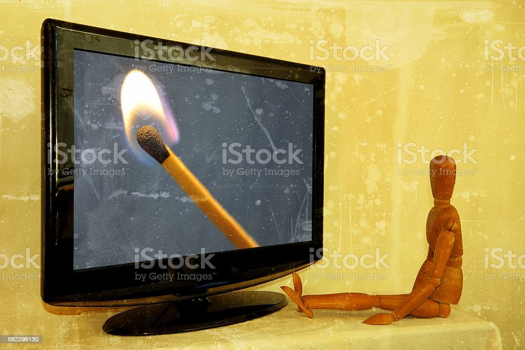 Dummy painter in front of television with lit match stock photo