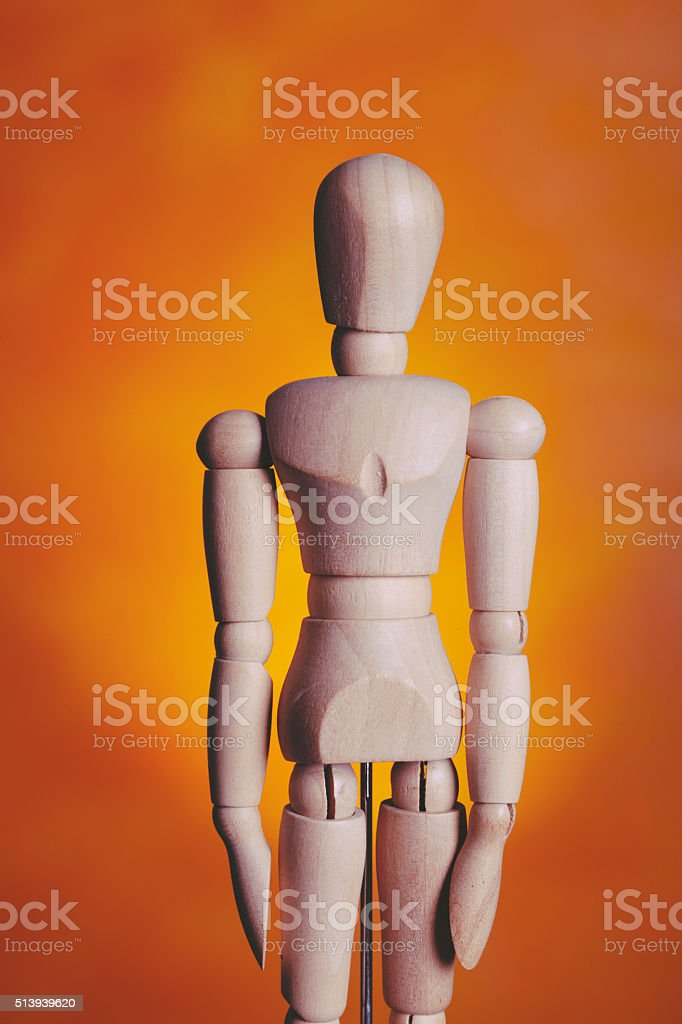 Dummy standing against orange background stock photo