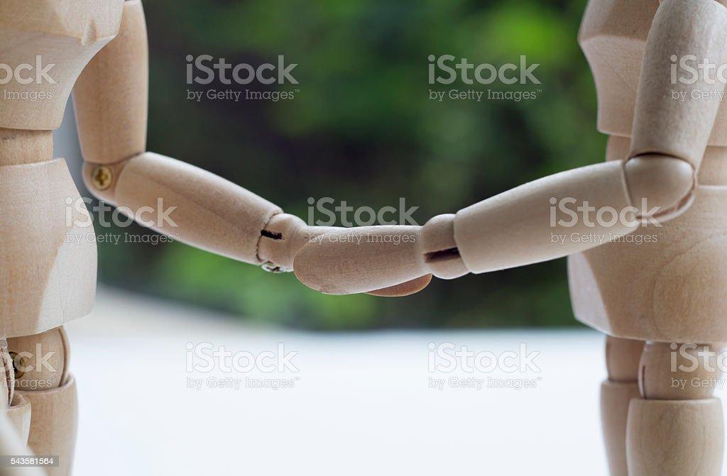 dummy wood man acting couple business shake hand stock photo