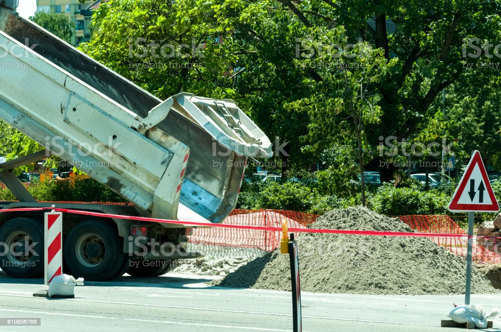 Dump tipper truck unload sand on the street construction site. Rear end of truck. stock photo
