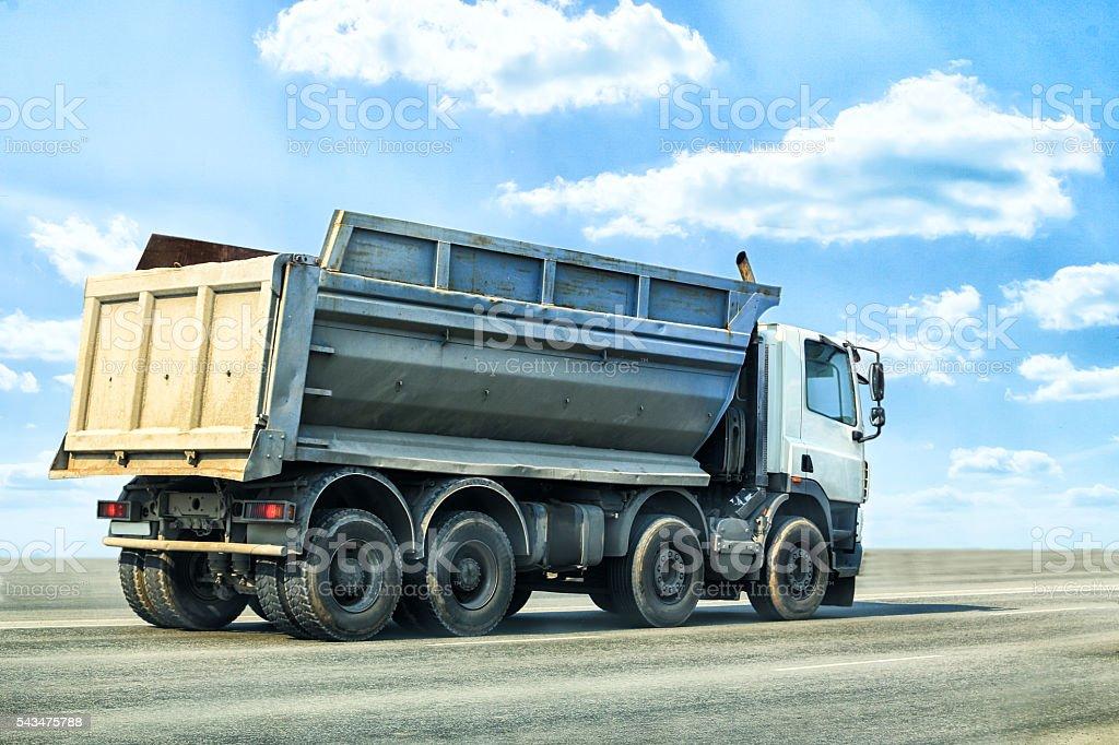 dump truck goes on highway stock photo