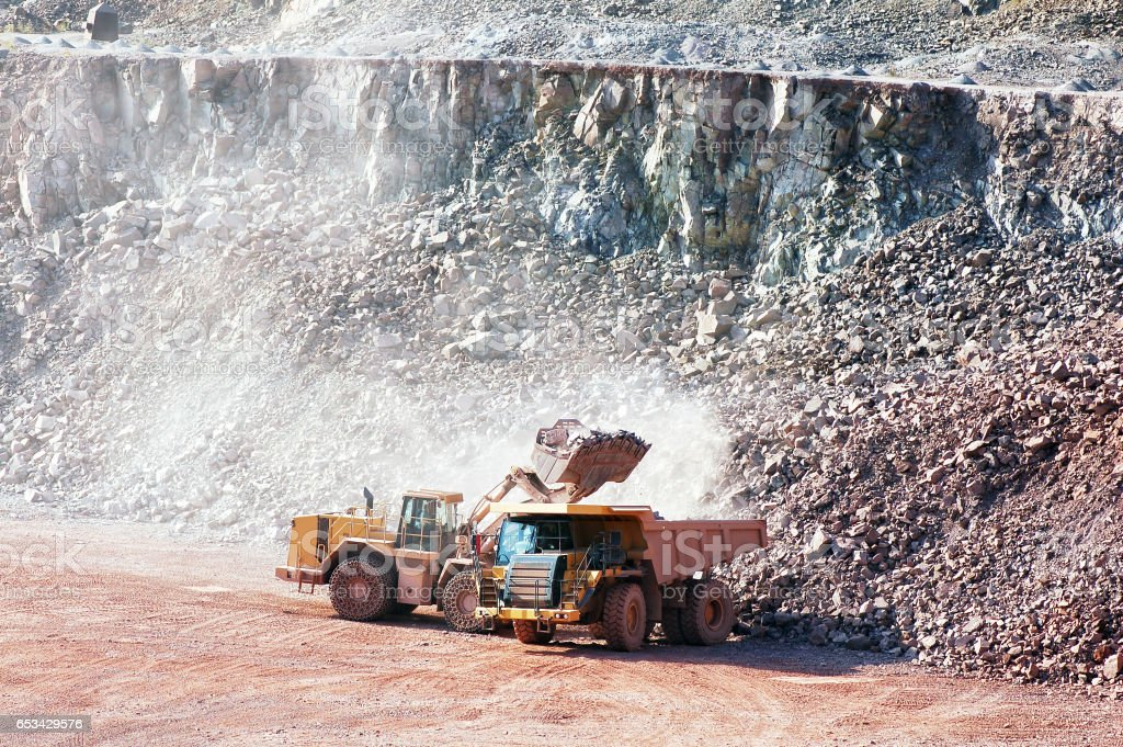 Dumper trucking getting loaded by earth mover with rocks. quarry stock photo