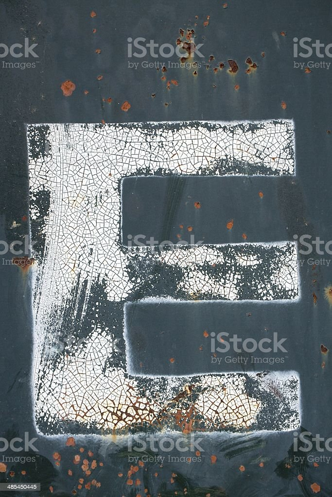 Dumpster Background with weathered E painted on it royalty-free stock photo