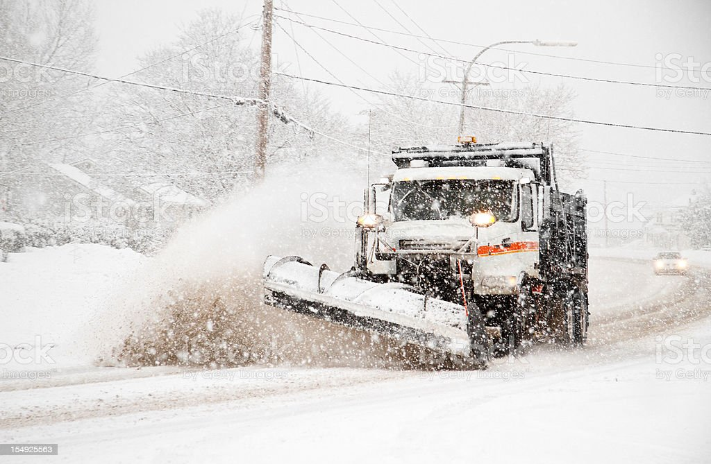 dumptruck with plow plowing snow during northeaster stock photo