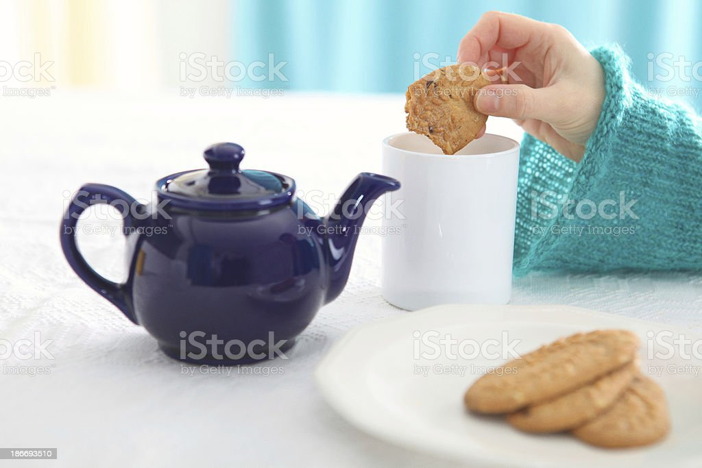 dunking biscuit into tea royalty-free stock photo