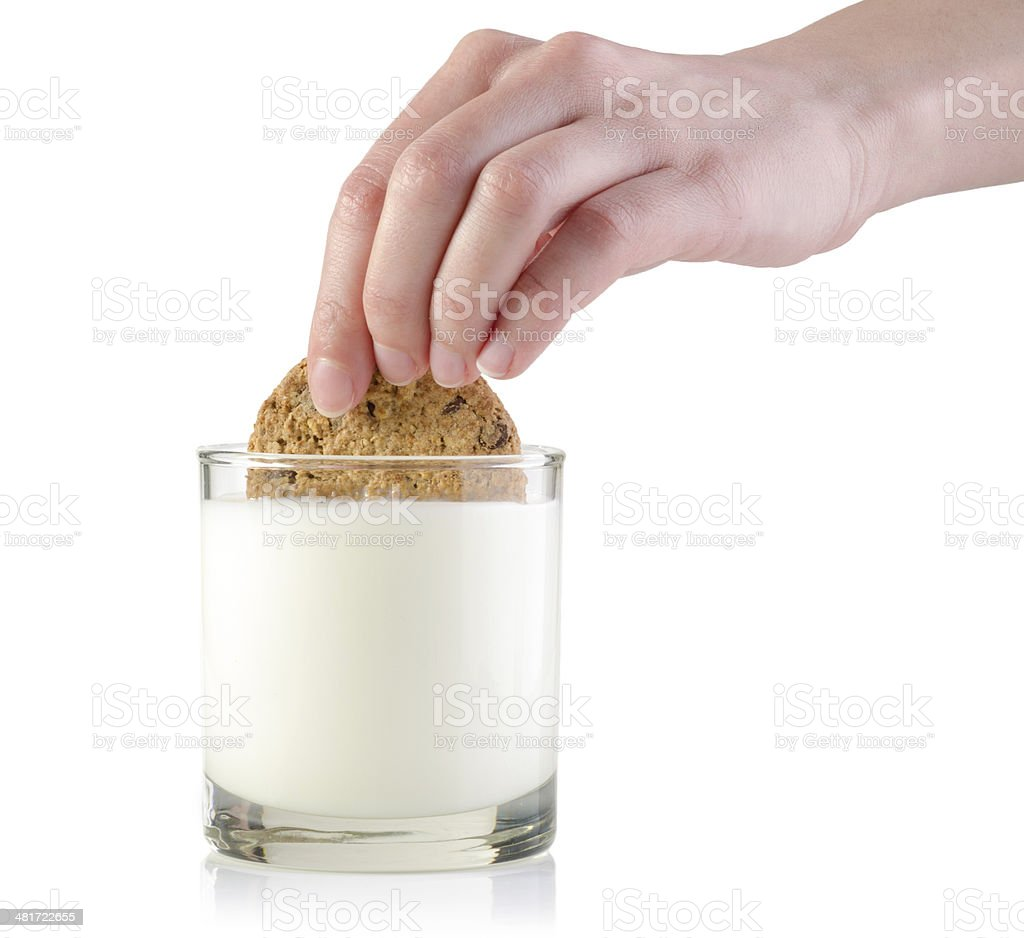 Dunking cookie in milk stock photo