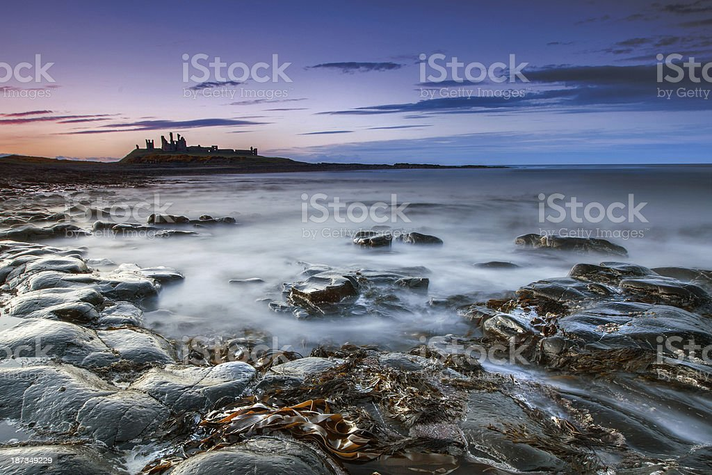 Dunstanburg Castle at dusk stock photo