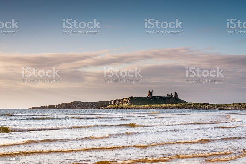 Dunstanburgh Castle above the sea stock photo