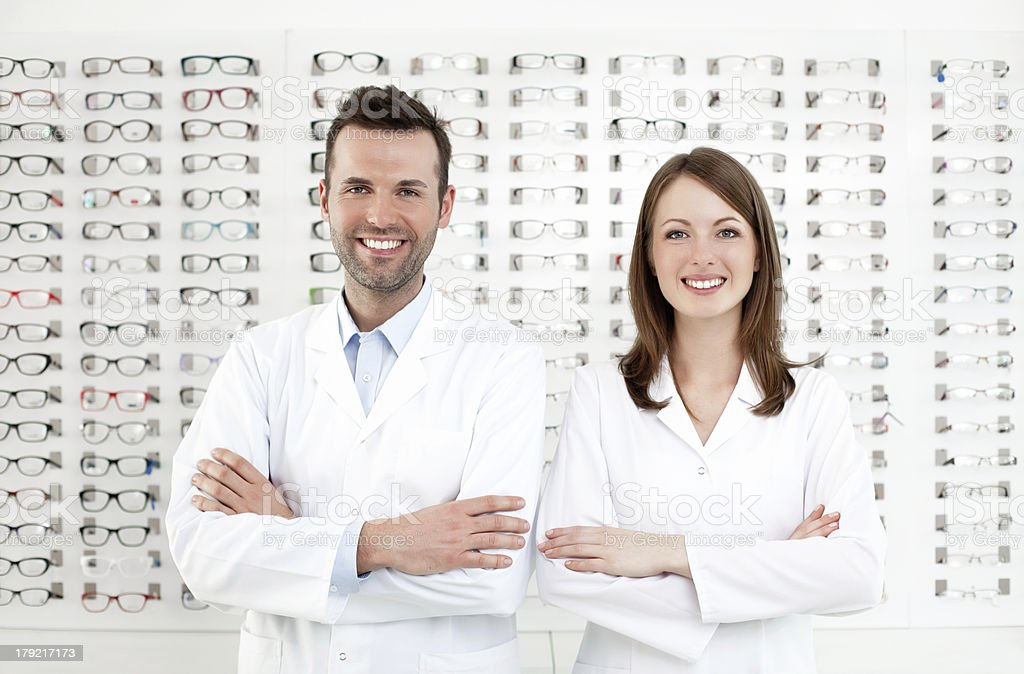 Duo of happy optometrists pose in front of wall of glasses stock photo