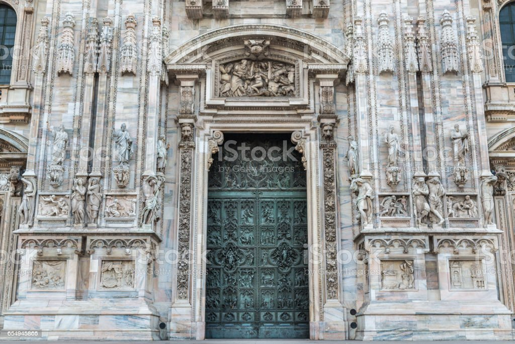 Duomo of Milan, Italy. Detail of facade and main entrance door to the famous cathedral of Milan in Duomo Square. stock photo