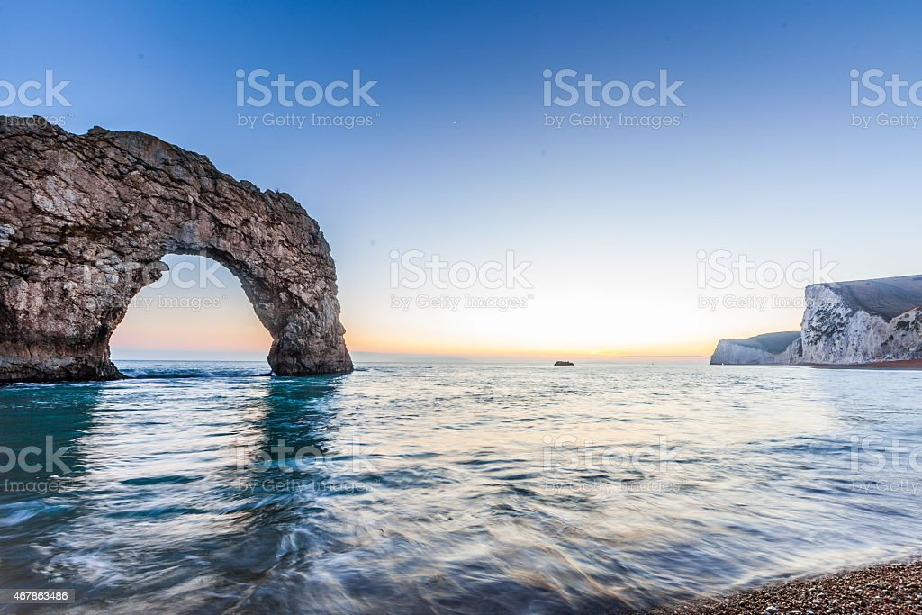 Durdle door at the shore by the ocean stock photo