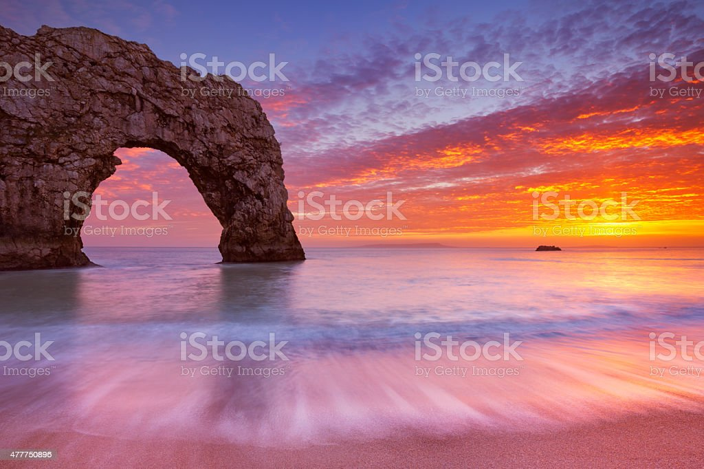 Durdle Door rock arch in Southern England at sunset stock photo