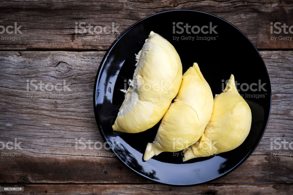 Durian on Black plate over wooden table. Top view. Tropical fruit. King of fruit. stock photo