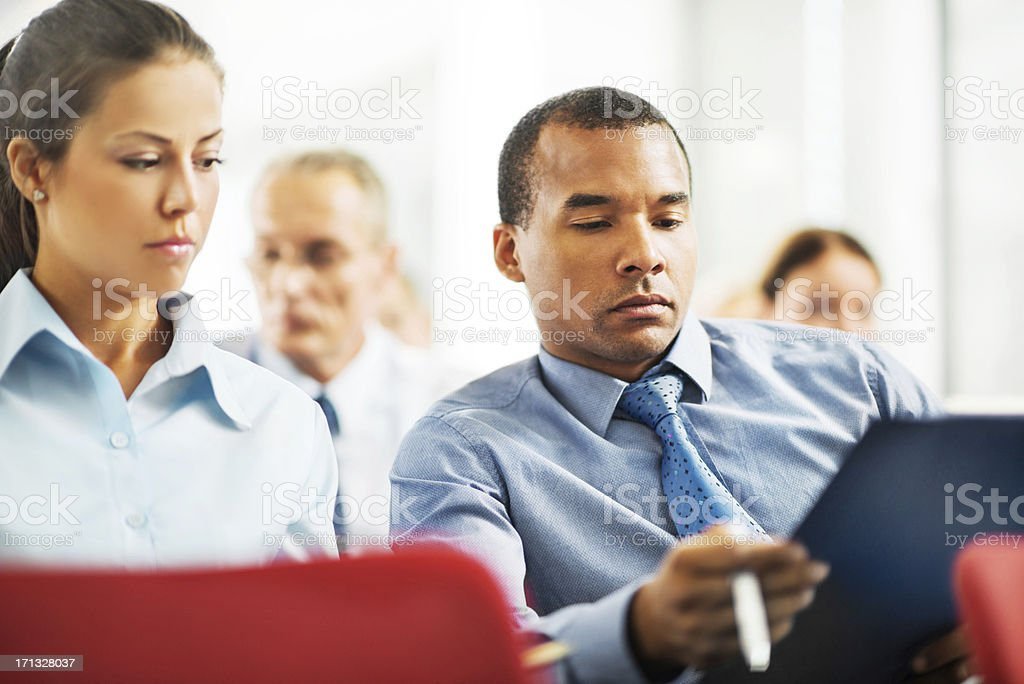 During a seminar two businesspeople are looking at reports. royalty-free stock photo