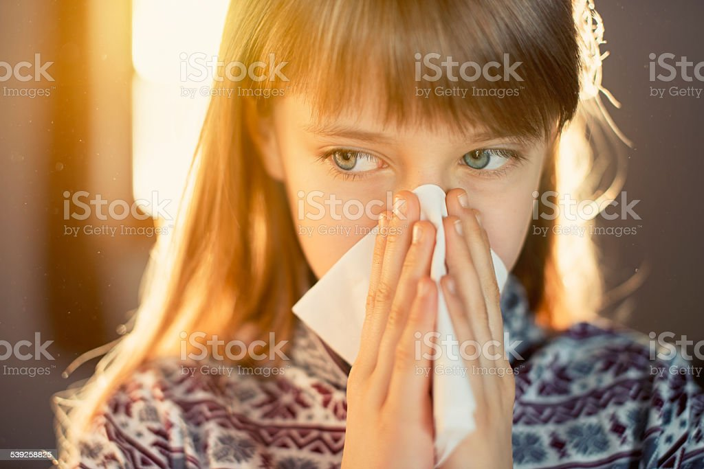 Little girl in dusty home cleaning nose. Dust particles visible in...