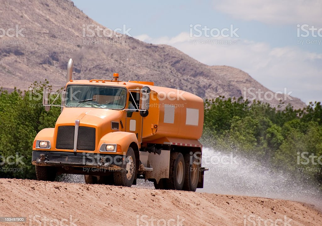 Dust Control With Water Truck on Dirt Road stock photo