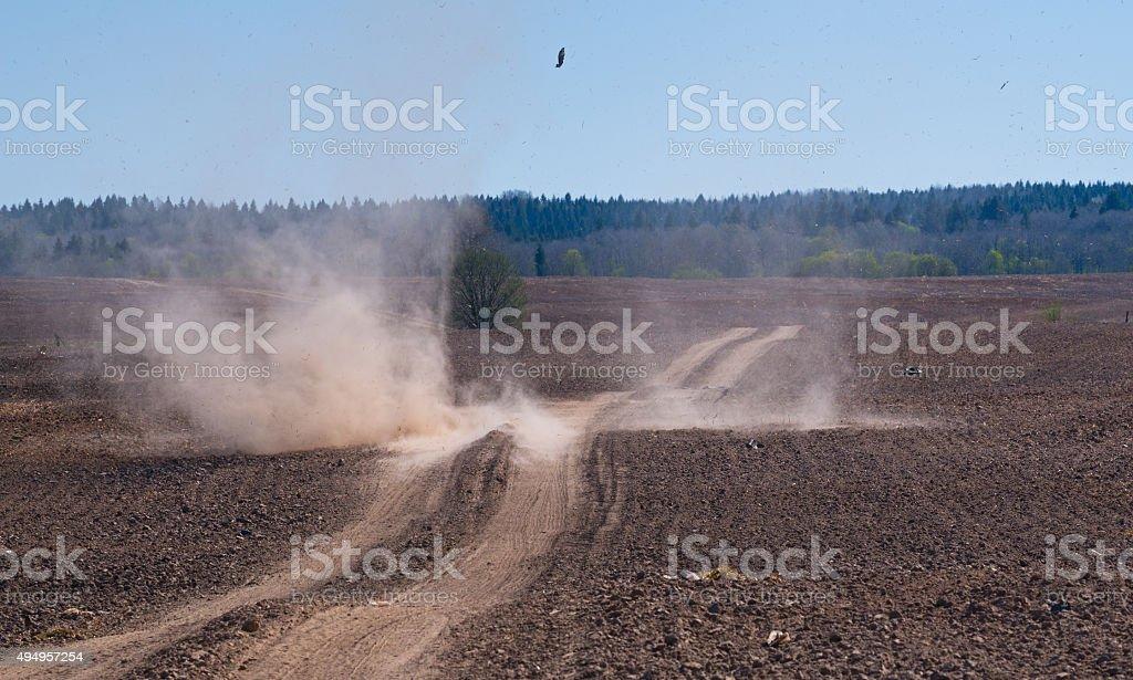 Dust devil crossing field road. stock photo
