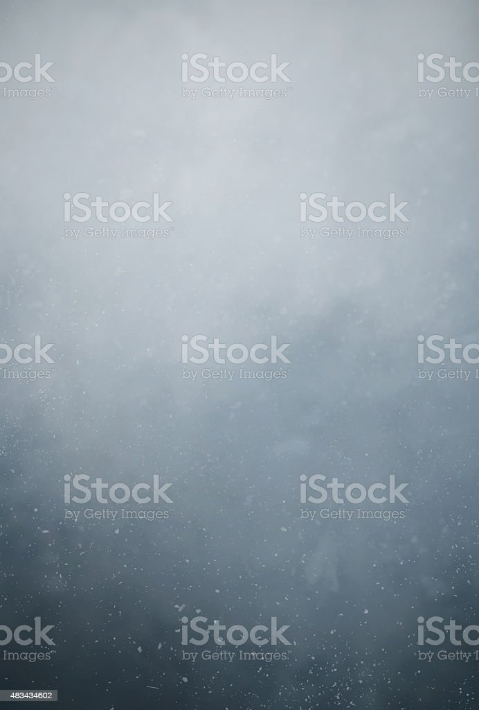 Dust particles floating in the air against dark background stock photo