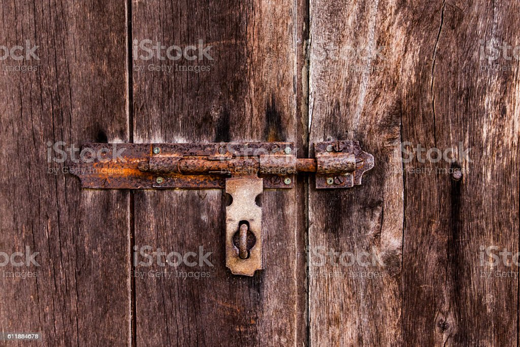 dusty bolt on grungy old wooden door. stock photo