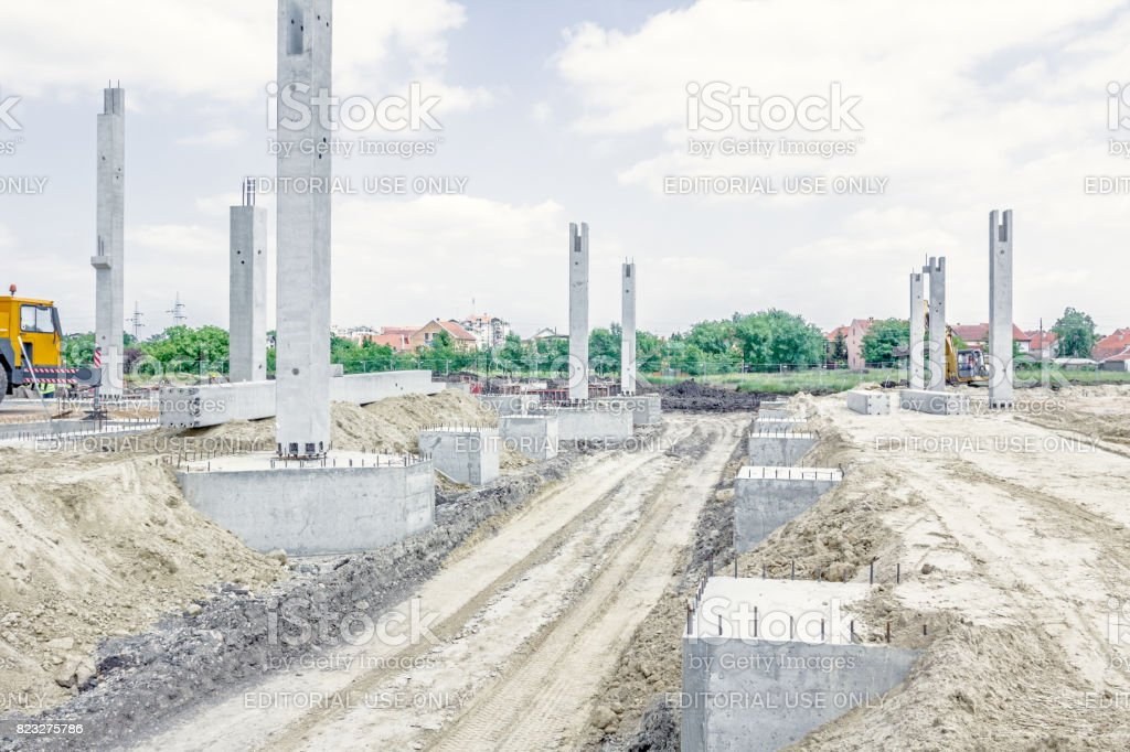 Dusty road with tire tracks of vehicles are among concrete pillar base of new edifice stock photo