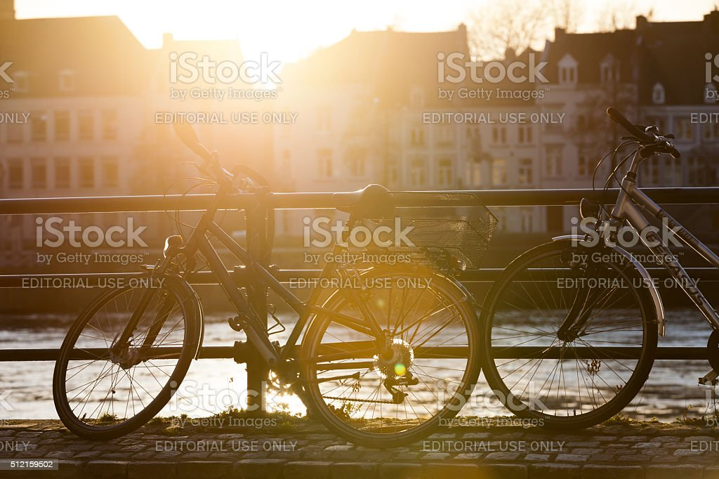 Dutch bicycles leaning against railings fence sun houses and river stock photo