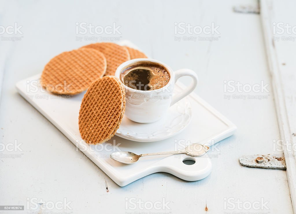 Dutch caramel stroopwafels and cup of black coffee on white stock photo