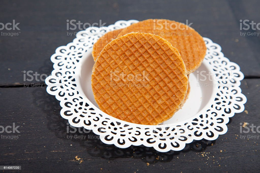 Dutch cookie stroopwafels on white plate on black wooden background stock photo