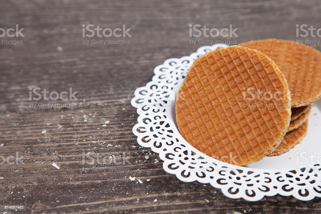 Dutch cookie stroopwafels on white plate on brown wooden background stock photo