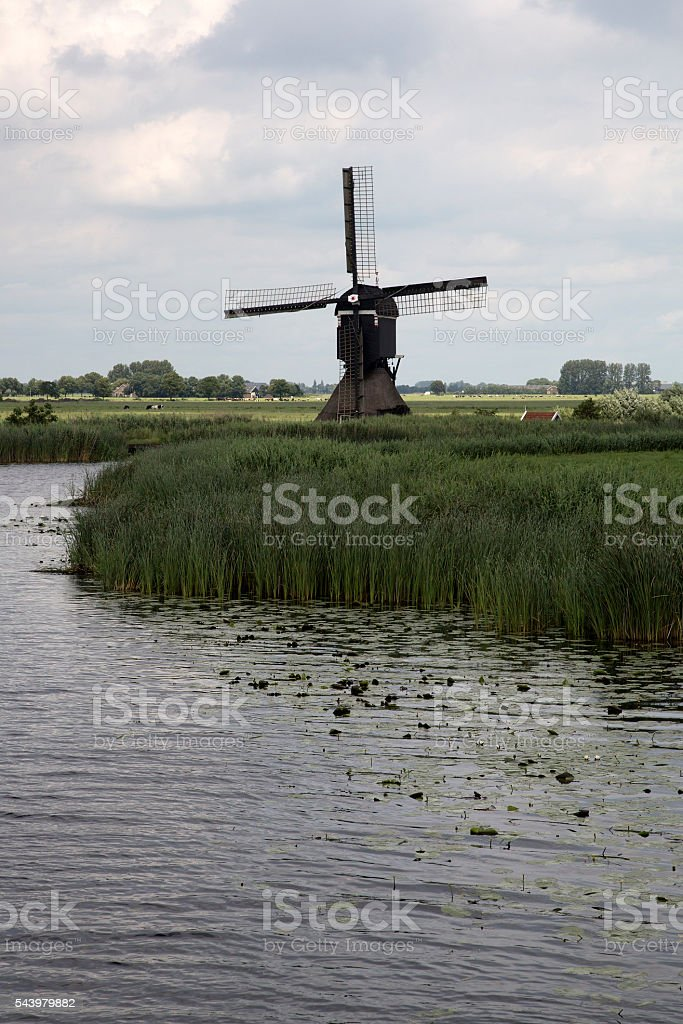 Dutch countryside with windmilll along canal stock photo