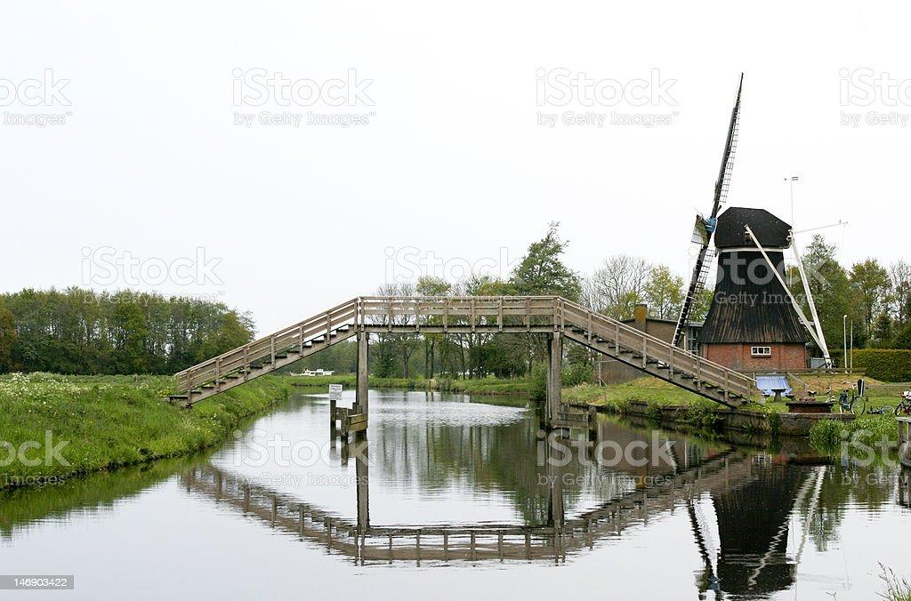 Dutch footbridge with windmill stock photo