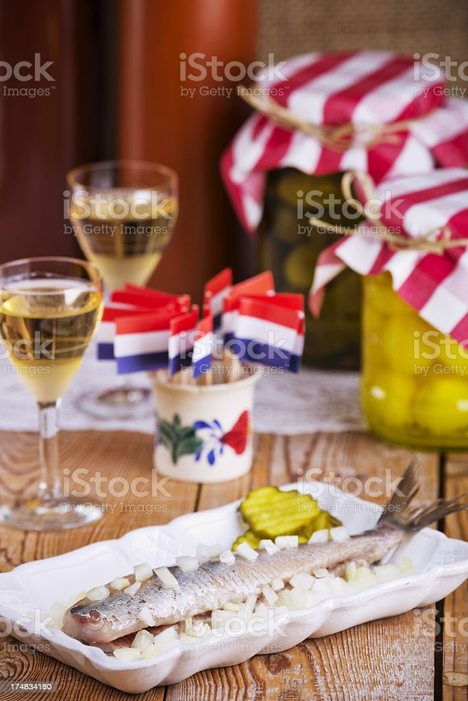 Dutch herring ('haring') with onions and pickles on rustic table stock photo