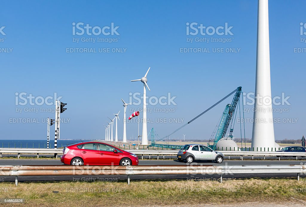 Dutch highway with cars along construction site wind turbines stock photo