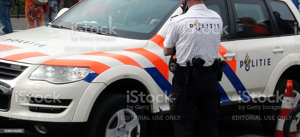 Dutch Police Officer Standing Close To Police Patrol Vehicle.Amstelveen stock photo