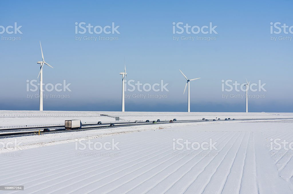 Dutch rural winter landscape with a highway and big windturbines royalty-free stock photo