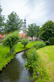 Dutch village with canal and church bell tower, The Netherlands