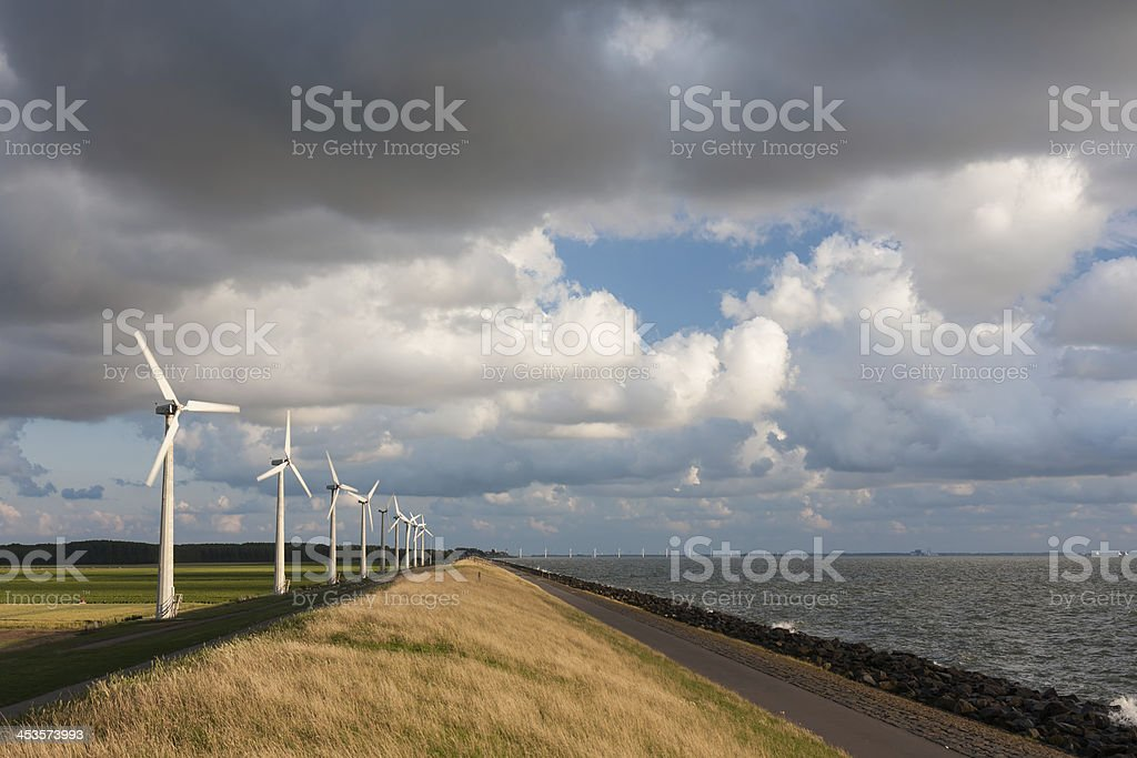 Dutch wind turbines and cloudscape in last sunlight summer evening royalty-free stock photo