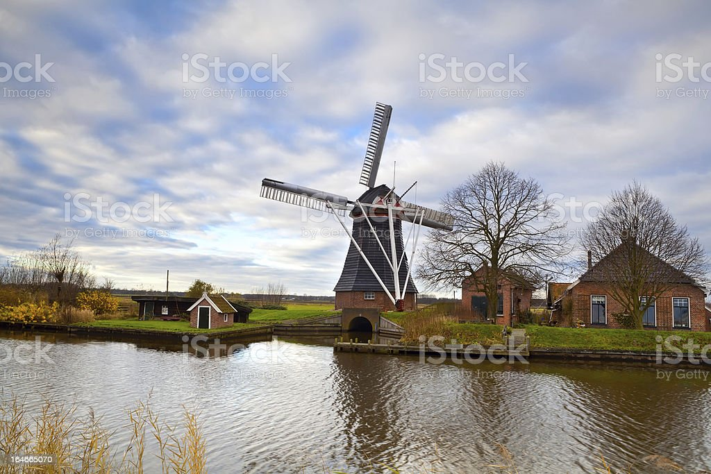 Dutch windmill by canal royalty-free stock photo