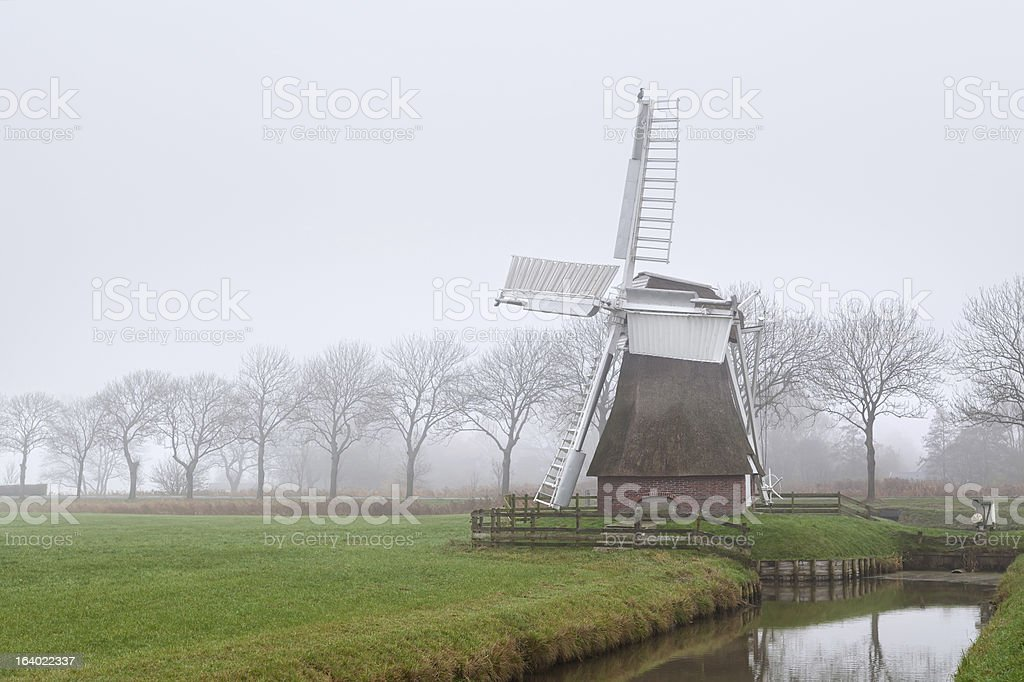 Dutch windmill in fog royalty-free stock photo