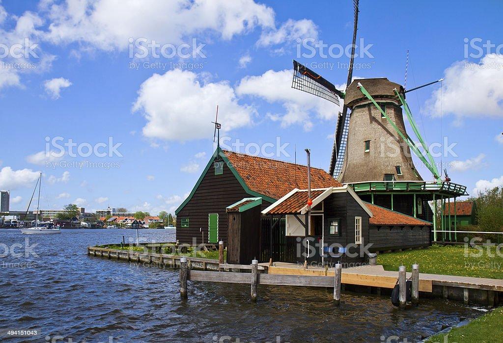 dutch windmill over river waters stock photo